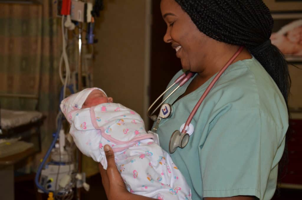 a nurse holding a newborn infant